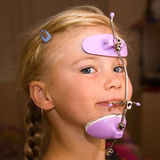 Young girl with headgear dentofacial orthopedics treatment