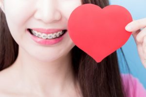 Smiling girl with braces in Milford holding a paper heart valentine