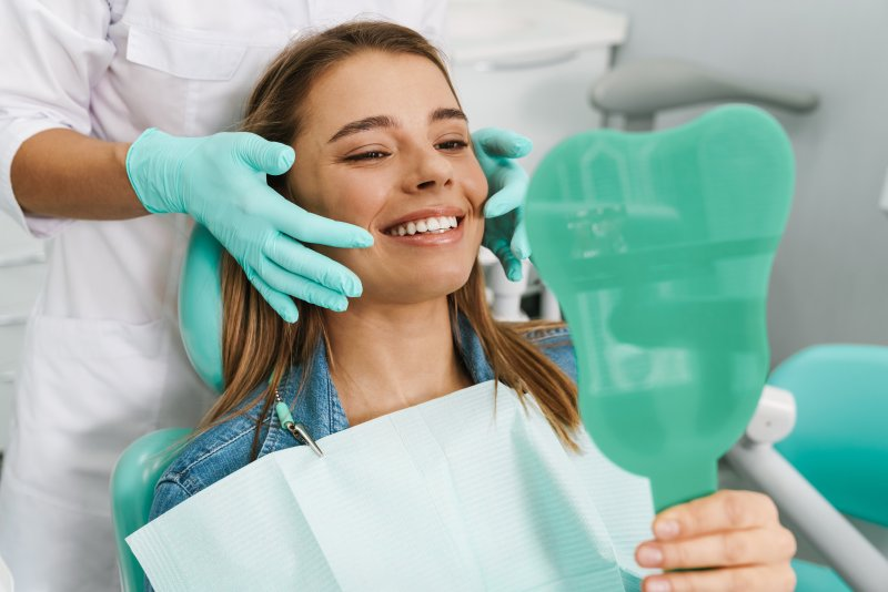 Young woman smiling while looking at teeth in mirror
